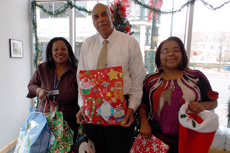 smiling people holding presents